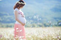 Πορτρέτο της όμορφης εγκύου γυναίκας στις φυσώντας φυσαλίδες τομέων στοκ εικόνες