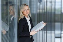 Πορτρέτο της όμορφης επιχειρηματία που χαμογελά και που στέκεται με το φάκελλο στο γραφείο στοκ εικόνες