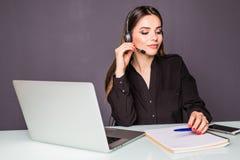 Πορτρέτο της όμορφης εργασίας επιχειρησιακών γυναικών στο γραφείο της με την κάσκα και το lap-top στην αρχή Στοκ Φωτογραφία