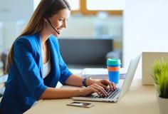 Πορτρέτο της όμορφης εργασίας επιχειρησιακών γυναικών στο γραφείο της με την κάσκα και το lap-top Στοκ Εικόνα