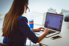 Πορτρέτο της όμορφης εργασίας επιχειρησιακών γυναικών στο γραφείο της με την κάσκα και το lap-top Στοκ Φωτογραφίες