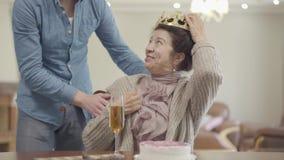 Πορτρέτο της όμορφης ηλικιωμένης γυναίκας Ο ενήλικος εγγονός φέρνει την κορώνα και την βάζει στο κεφάλι της γιαγιάς, ανώτερη κυρί απόθεμα βίντεο