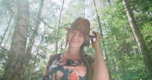 Πορτρέτο της όμορφης καυκάσιας γυναίκας σε ένα δασικό φορώντας καπέλο που χαμογελά σε μια κάμερα απόθεμα βίντεο