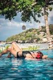 Πορτρέτο της όμορφης μαυρισμένης γυναίκας στη μαύρη swimwear χαλάρωση στη SPA πισινών Καυτή θερινή ημέρα και φωτεινός ηλιόλουστος Στοκ Εικόνες