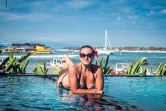 Πορτρέτο της όμορφης μαυρισμένης γυναίκας στη μαύρη swimwear χαλάρωση στη SPA πισινών Καυτή θερινή ημέρα και φωτεινός ηλιόλουστος Στοκ Φωτογραφία