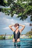 Πορτρέτο της όμορφης μαυρισμένης γυναίκας στη μαύρη swimwear χαλάρωση στη SPA πισινών Καυτή θερινή ημέρα και φωτεινός ηλιόλουστος Στοκ εικόνες με δικαίωμα ελεύθερης χρήσης
