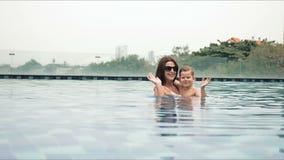 Πορτρέτο της όμορφης μητέρας με το γιο της που στέκεται στην πισίνα και γελώντας κατά τη διάρκεια των διακοπών τη θερμή θερινή ημ φιλμ μικρού μήκους