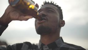 Πορτρέτο της όμορφης μπύρας κατανάλωσης ατόμων αφροαμερικάνων που εξετάζει τη κάμερα υπαίθρια Ο ηλιόλουστος ελαφρύς ουρανός απόθεμα βίντεο