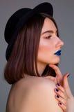Πορτρέτο της όμορφης νέας γυναίκας με τα μπλε χείλια και στο καπέλο μπαζούκας Στοκ Φωτογραφίες