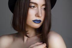 Πορτρέτο της όμορφης νέας γυναίκας με τα μπλε χείλια και στο καπέλο μπαζούκας Στοκ Εικόνες