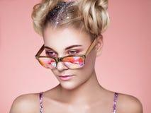 Πορτρέτο της όμορφης νέας γυναίκας με τα χρωματισμένα γυαλιά στοκ εικόνα
