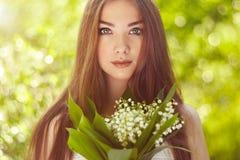 Πορτρέτο της όμορφης νέας γυναίκας με τον κρίνο της κοιλάδας στοκ φωτογραφία με δικαίωμα ελεύθερης χρήσης