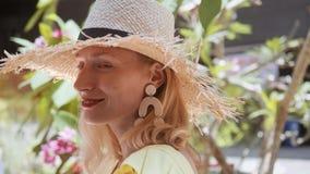 Πορτρέτο της όμορφης νέας γυναίκας με το καπέλο αχύρου μια ηλιόλουστη ημέρα που εξετάζει τη κάμερα φιλμ μικρού μήκους