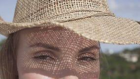 Πορτρέτο της όμορφης νέας γυναίκας με το καπέλο αχύρου μια ηλιόλουστη ημέρα που εξετάζει τη κάμερα πέρα από το μπλε ουρανό και το φιλμ μικρού μήκους