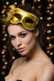 Πορτρέτο της όμορφης νέας γυναίκας που φορά τη χρυσή μάσκα κομμάτων Στοκ εικόνα με δικαίωμα ελεύθερης χρήσης