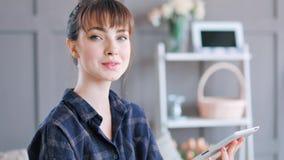 Πορτρέτο της όμορφης νέας γυναίκας στις πυτζάμες που κρατά τη συνεδρίαση PC ταμπλετών στο σύγχρονο εγχώριο εσωτερικό απόθεμα βίντεο