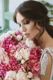 Πορτρέτο της όμορφης νέας γυναίκας brunette με τις ιδιαίτερες προσοχές και τα μεγάλα σαγηνευτικά χείλια, με την ανθοδέσμη των λου Στοκ Εικόνες