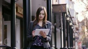 Πορτρέτο της όμορφης νέας επιχειρηματία που χρησιμοποιούν τη συσκευή ταμπλετών στην οδό στο ηλιοβασίλεμα κοντά στην επιχείρηση απόθεμα βίντεο