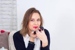 Πορτρέτο της όμορφης νέας επιχειρησιακής γυναίκας με τα ξανθά μαλλιά που βάζει το κόκκινο κραγιόν εξετάζοντας τη κάμερα με το χαμ Στοκ Εικόνα