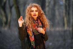 Πορτρέτο της όμορφης νέας κοκκινομάλλους γυναίκας στο παλτό ελιών Να θέσει στο δάσος υπαίθρια στοκ φωτογραφία