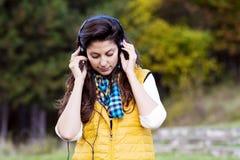 Πορτρέτο της όμορφης νέας μουσικής ακούσματος γυναικών υπαίθριας απόλαυση της μουσικής Στοκ Εικόνες