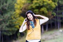 Πορτρέτο της όμορφης νέας μουσικής ακούσματος γυναικών υπαίθριας απόλαυση της μουσικής Στοκ Εικόνα