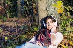 Πορτρέτο της όμορφης νέας μουσικής ακούσματος γυναικών υπαίθριας απόλαυση της μουσικής Στοκ φωτογραφία με δικαίωμα ελεύθερης χρήσης