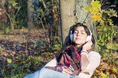 Πορτρέτο της όμορφης νέας μουσικής ακούσματος γυναικών υπαίθριας απόλαυση της μουσικής Στοκ εικόνες με δικαίωμα ελεύθερης χρήσης