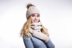 Πορτρέτο της όμορφης νέας ξανθής γυναίκας που φορά το θερμά πλεκτά πουλόβερ, το καπέλο, το μαντίλι και τα γάντια στο άσπρο υπόβαθ στοκ εικόνες