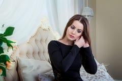 Πορτρέτο της όμορφης νέας συνεδρίασης γυναικών brunette στην κρεβατοκάμαρα, που βάζει το σκουλαρίκι επάνω Στοκ εικόνες με δικαίωμα ελεύθερης χρήσης