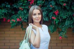 Πορτρέτο της όμορφης νέας χαμογελώντας γυναίκας, που κρατά την τσάντα δέρματος Στοκ Φωτογραφία