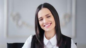 Πορτρέτο της όμορφης νέας χαμογελώντας επιχειρηματία brunette που θέτει και που εξετάζει τη κάμερα φιλμ μικρού μήκους