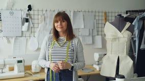 Πορτρέτο της όμορφης νέας seamstress γυναικών στάσης στον εργασιακό χώρο, σχετικά με τη μέτρηση της ταινίας και την εξέταση τη κά φιλμ μικρού μήκους