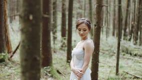 Πορτρέτο της όμορφης νύφης με τη γαμήλια ανθοδέσμη των λουλουδιών που στέκονται στο βρύο στο δάσος πεύκων φιλμ μικρού μήκους