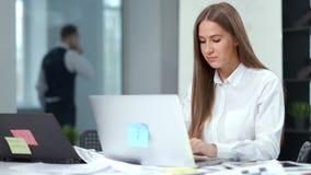 Πορτρέτο της όμορφης σκεπτικής επιχειρηματία που εργάζεται χρησιμοποιώντας το lap-top στο σύγχρονο γραφείο φιλμ μικρού μήκους