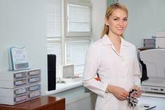 Πορτρέτο της όμορφης στάσης γιατρών ματιών με την οφθαλμολογική συσκευή στο γραφείο στοκ εικόνα