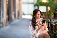 Πορτρέτο της όμορφης συνεδρίασης γυναικών στον υπαίθριο καφέ κατανάλωσης καφέδων και χρησιμοποίηση του smartphone Νέο κορίτσι που στοκ εικόνες με δικαίωμα ελεύθερης χρήσης