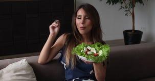 Πορτρέτο της όμορφης χαμογελώντας γυναίκας που τρώει την ορεκτική σαλάτα που κάνει το φιλί αέρα το μέσο πυροβολισμό φιλμ μικρού μήκους