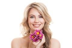 Πορτρέτο της όμορφης χαμογελώντας γυναίκας με τα λουλούδια σαφές δέρμα Στοκ Φωτογραφία