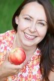 Πορτρέτο της ώριμης γυναίκας που τρώει τη φρέσκια Apple Στοκ Φωτογραφία