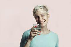 Πορτρέτο του άσπρου νέου ομορφιάς χαμόγελου τρίχας γυναικών σύντομου με το ποτήρι του νερού Στοκ εικόνες με δικαίωμα ελεύθερης χρήσης