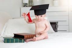 Πορτρέτο του έξυπνου αγοράκι στη συνεδρίαση mortarboard ΚΑΠ με τα βιβλία στην κρεβατοκάμαρα Στοκ Εικόνες