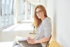 Πορτρέτο του έξυπνου σπουδαστή με την ανοικτή ανάγνωση βιβλίων αυτό στο κολλέγιο Όμορφη γυναίκα σπουδαστής σε ένα πανεπιστήμιο, γ Στοκ Εικόνα