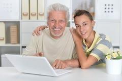 Πορτρέτο του αγοριού και του παππού με ένα lap-top Στοκ Φωτογραφίες