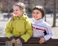 Πορτρέτο του αγοριού και του ξανθού κοριτσιού σε έναν πάγκο το ινδικό καλοκαίρι Στοκ Εικόνα