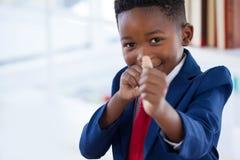 Πορτρέτο του αγοριού που μιμείται ως επιχειρηματία το παιχνίδι με τη λαστιχένια ζώνη Στοκ Φωτογραφίες