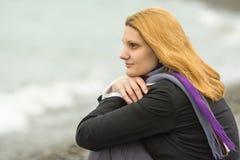 Πορτρέτο του αινιγματικού χαμογελώντας κοριτσιού στο υπόβαθρο της κυματωγής μια νεφελώδη κρύα ημέρα Στοκ Εικόνες