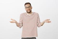 Πορτρέτο του ανίδεου απληροφόρητου όμορφου τύπου στα γυαλιά, απαξιώντας με τους φοίνικες και την αδέξια έκφραση, που είναι ταραγμ στοκ εικόνες με δικαίωμα ελεύθερης χρήσης