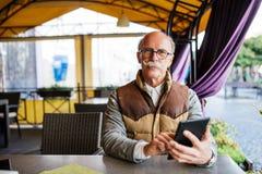 Πορτρέτο του ανώτερου ατόμου που χρησιμοποιεί την ψηφιακή ταμπλέτα στον καφέ, εστίαση σε ετοιμότητα αρσενικά που κρατούν τη σύγχρ Στοκ εικόνες με δικαίωμα ελεύθερης χρήσης