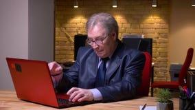 Πορτρέτο του ανώτερου ατόμου στα γυαλιά και το επίσημο κοστούμι που λειτουργούν με το lap-top που ενοχλείται και που ενοχλείται σ απόθεμα βίντεο
